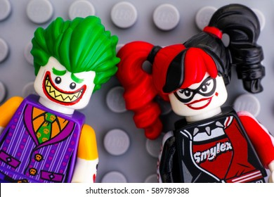 Tambov, Russian Federation - February 11, 2017 Two Lego Batman Movie minifigures -  The Joker and Harley Quinn - on Lego gray baseplate background. Studio shot.