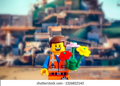 Tambov, Russian Federation - February 24, 2019 Lego Hard Hat Emmet minifigure with flowers against Apocalypseburg background. The Lego Movie 2.