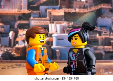 Tambov, Russian Federation - February 24, 2019 Lego Hard Hat Emmet and Lucy minifigures looking at each other and laugh against Apocalypseburg background. The Lego Movie 2.
