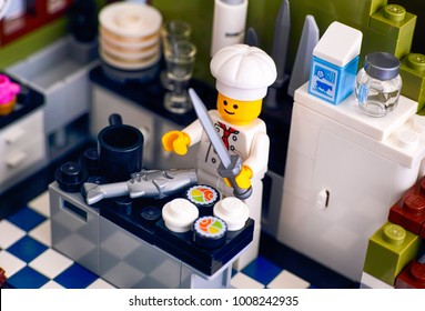 Tambov, Russian Federation - January 04, 2018 Lego chef cooking sushi and fish in the kitchen. Studio shot.
