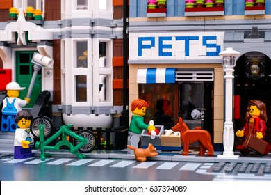Tambov, Russian Federation - January 04, 2017 Lego street. Painter painting house wall. Girl repairs bike. Man with bone stand near pet shop with dog and cat. Woman with suitcase walking down street.