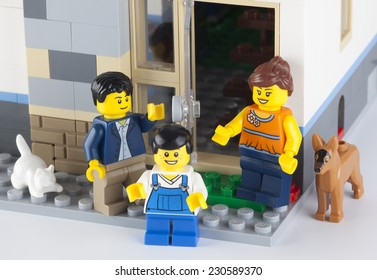 Tambov, Russian Federation - January 08, 2014 Happy LEGO family standing near his home with pets. There are minifigures of mom, dad, son, cat and dog.