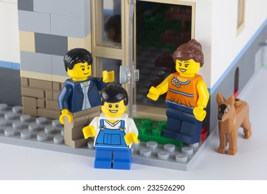 Tambov, Russian Federation - January 08, 2014 Happy LEGO family standing near his home with dog. There are minifigures of mom, dad, son, and dog. Studio shot.