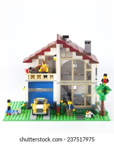 Tambov, Russian Federation - January 08, 2014 LEGO Family House with yellow car and couple minifigures on white background.  Lego manufactured by the Lego Group (Billund, Denmark).