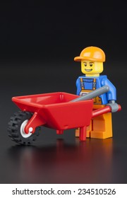 Tambov, Russian Federation - January 11, 2014 LEGO worker minifigure with red empty barrow and shovel on black background.