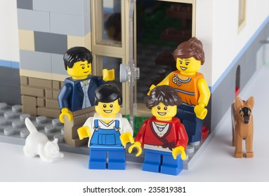 Tambov, Russian Federation - January 12, 2014 Happy LEGO family standing near his home with pets. There are minifigures of mom, dad, son, daughter, cat and dog.