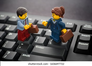 Tambov, Russian Federation - January 24, 2020 Lego businessman and businesswoman minifigures standing on a black computer keyboard.