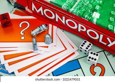 Tambov, Russian Federation - January 26, 2018 Monopoly Board Game box, Chance cards, tokens, dices om gameboard. Studio shot.