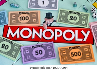 Tambov, Russian Federation - January 26, 2018 Center of Monopoly gameboard with money packs tokens and dice. Studio shot.