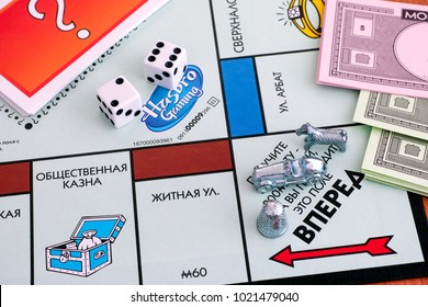 Tambov, Russian Federation - January 26, 2018 Monopoly Board Game. Three tokens on field Go of gameboard with two dices, money and Chance cards. Studio shot.