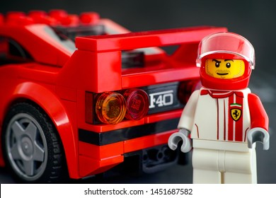 Tambov, Russian Federation - July 02, 2019 Lego Ferrari F40 Competizione driver minifigure by LEGO Speed Champions standing back his car. Studio shot.