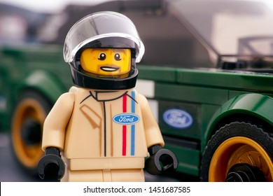 Tambov, Russian Federation - July 02, 2019 Lego 1968 Ford Mustang Fastback driver minifigure by LEGO Speed Champions and his car on background. Studio shot.