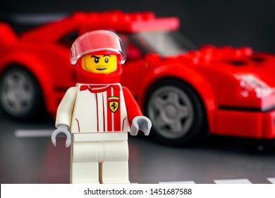 Tambov, Russian Federation - July 02, 2019 Lego Ferrari F40 Competizione driver minifigure by LEGO Speed Champions against his car. Studio shot.