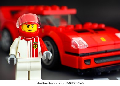 Tambov, Russian Federation - July 02, 2019 Lego Ferrari F40 Competizione driver minifigure against his car by LEGO Speed Champions. Road baseplate background;