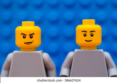 Tambov, Russian Federation - July 24, 2016 Two Lego minifigures - one strict and one smiling. Blue background. Studio shot.