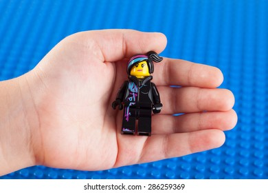 Tambov, Russian Federation - July 26, 2014 Lego Wyldstyle minifigure in child hand against Lego blue baseplate background. Studio shot.