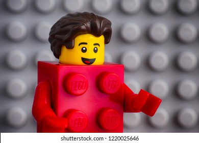 Tambov, Russian Federation - July 29, 2018 Lego Red Suit Brick Guy minifigure against gray baseplate background. Studio shot.