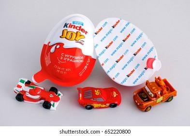 Tambov, Russian Federation - June 01, 2017 Kinder Joy eggs with three Kinder Cars toys on gray background. Kinder Joy manufactured by Italian company Ferrero. Studio shot.