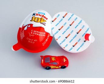 Tambov, Russian Federation - June 01, 2017 Kinder Joy eggs with Lightning McQueen car toy on gray background. Kinder Joy manufactured by Italian company Ferrero. Studio shot.
