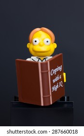 Tambov, Russian Federation - June 08, 2015 Lego Martin Prince minifigure with book on black background. Studio shot.