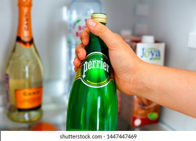Tambov, Russian Federation - June 10, 2019 Woman hand taking out bottle with Perrier water from the fridge. Close-up.