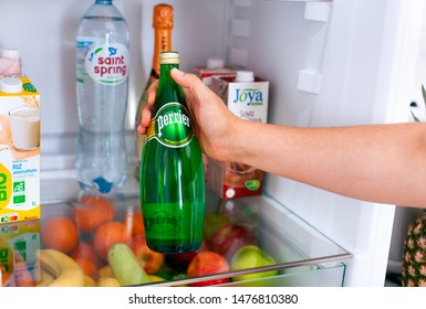 Tambov, Russian Federation - June 10, 2019 Person hand taking out Perrier water bottle from the fridge.