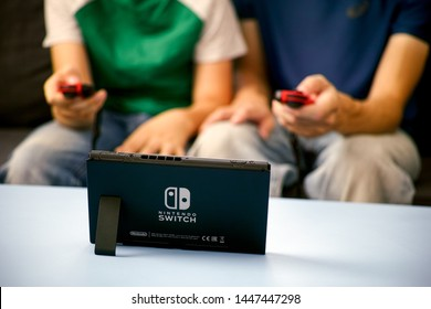 Tambov, Russian Federation - June 22, 2019 Man and kid playing Nintendo Switch video game console.