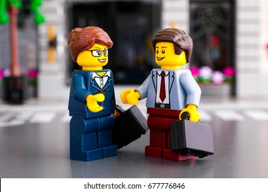 Tambov, Russian Federation - June 22, 2017 Lego businessman and businesswoman with suitcases meet on the street. Studio shot.