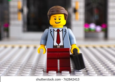 Tambov, Russian Federation - June 22, 2017 Lego businessman with suitcase stay on the street. Studio shot.