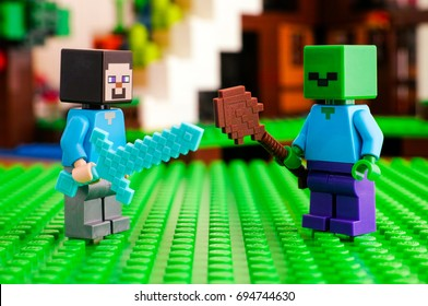 Tambov, Russian Federation - June 25, 2017 LEGO Minecraft. Steve fighting zombie. Green baseplate background. Studio shot.