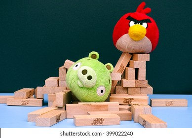 Tambov, Russian Federation - March 03, 2016 Angry Bird vs. Bad Piggies. Red bird broke bad pigs house. Bad piggy lying in pile of Jenga bricks which its house was made out of.. Studio shot.