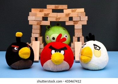 Tambov, Russian Federation - March 03, 2016 Bomb, Matilda and Red Angry Birds standing in front of Bad Piggy sitting inside of house, made from Jenga bricks. Studio shot.