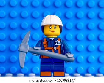 Tambov, Russian Federation - March 09, 2018 Lego miner minifiger with pickaxe against blue baseplate backgrounds.