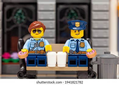 Tambov, Russian Federation - March 19, 2021 Lego policeman and policewoman minifigures sitting on a bench and drinking coffee and eating donuts.