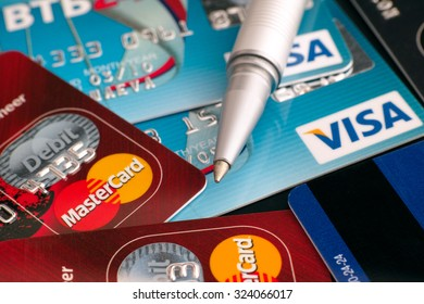 Tambov, Russian Federation - March 31, 2015 Visa and Mastercard credit cards with ballpoint pen on black background. Studio shot.