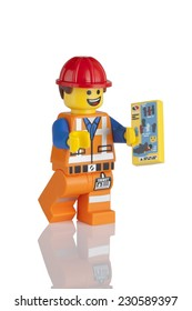 Tambov, Russian Federation - May 16, 2014 LEGO Hard Hat Emmet minifigure with instructions booklet on white background. LEGO Movie series. Studio shot.