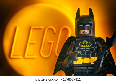 Tambov, Russian Federation - May 20, 2018 Lego Batman minifigure against yellow background with word LEGO. Studio shot.