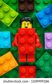 Tambov, Russian Federation - May 20, 2018 Lego Red Suit Brick Guy minifigure on green baseplate background with some colorful Lego bricks. Studio shot.