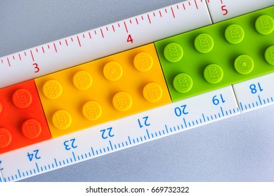 Tambov, Russian Federation - May 20, 2017 Lego ruler with inches and centimeters made from Lego bricks. Gray background. Studio shot.