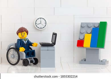 Tambov, Russian Federation - November 14, 2020 Lego minifigure businesswoman in a wheelchair in her office.