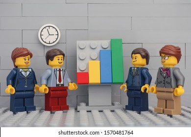 Tambov, Russian Federation - November 23, 2019 Lego minifigure businessmen having a meeting and discussing graphs showing the results of their successful teamwork.