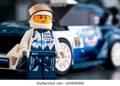 Tambov, Russian Federation - October 18, 2019 Lego Ford Fiesta M-Sport WRC driver minifigure by LEGO Speed Champions against his car on background. Studio shot.