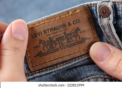 Tambov, Russian Federation- October 21, 2012: Woman's hand taking out label logo  from pocket of a pair Levi's Jeans. Studio shot. Levi Strauss &Co. is a American clothing company was founded in 1853.