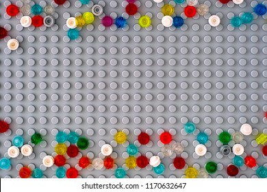 Tambov, Russian Federation - September 02, 2018 Lego gray baseplate with scattered Round Bricks 1x1. Studio shot.