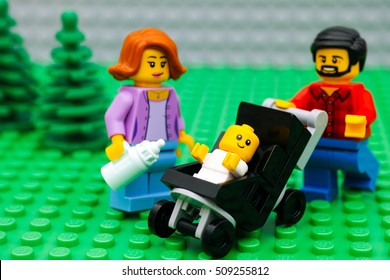 Tambov, Russian Federation - September 21, 2016 Lego family in park. Lego family minifigures - father, mother and baby in stroller. Studio shot.