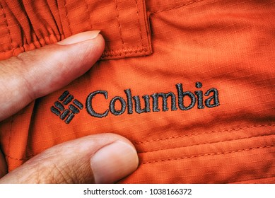 Tambov, Russian Federation - September 27, 2017 Embroidered logo Columbia on red clothes between person fingers. Close-up.