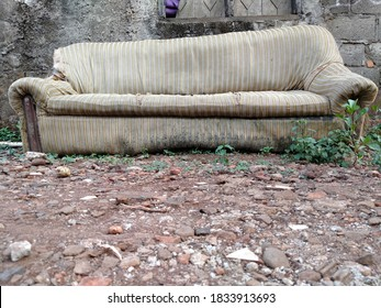 Tambun, Bekasi, Indonesia - October 12, 2020 : The unused sofa sits outside against the rocky ground in the foreground
