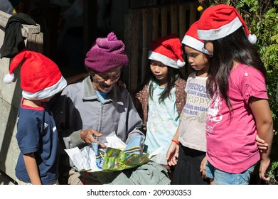 Tambunan, Sabah Malaysia. December 24, 2012 : A group of children visiting their elderly neighbour to give him a Chiristmas present on Christmas eve.