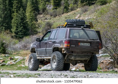 Tamga/Kyrgyzstan - May 2018:  Big 4wd lift Jeep Cherokee with huge truck drive offroad around Yssyk-Kul lake. Travelling in the mountains by car. Safari adventure. Central Asia expedition.