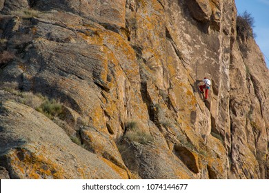 Tamgaly, Almaty area/Kazakhstan - March 2018: The brave rock climber climb on the yellow steep cliff with equipment. Best summer sport activity, rock climbing and trekking in Almaty mountains.